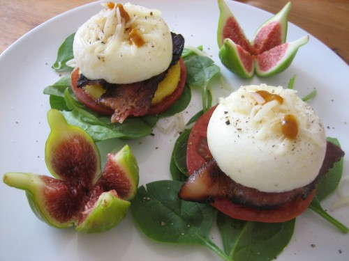 poached eggs with tomato, bacon, heirloom tomato and polenta on spinach